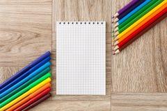 Viele sortierte Farbmarkierungsstifte und -bleistifte mit Notizblock Stockfotografie