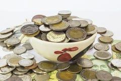 Viele Stapel von Münzenbaht Thailand-Währung in der gelben keramischen Schüssel Stockfoto