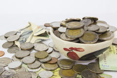 Viele Stapel von Münzenbaht Thailand-Währung in der gelben keramischen Schüssel Stockfotografie