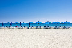 Viele Strandstühle und -regenschirme auf weißer Sandwüste setzen mit einem blauen Himmel auf den Strand Lizenzfreie Stockfotografie