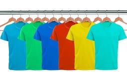 Viele T-Shirts auf den Aufhängern lokalisiert auf Weiß lizenzfreie stockfotografie