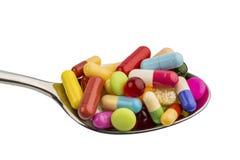 Viele Tabletten auf Löffel Stockbilder