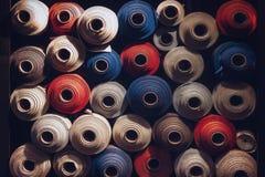 Viele Textilrollen von blauen, weißen und orange Farben stapelten ein über dem anderen stockbilder