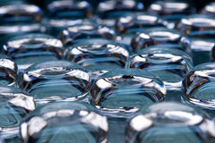 Viele transparenten Gläser auf blauem Hintergrund Lizenzfreie Stockfotos