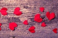 Viele Valentinsgrußherzen auf dem alten Holztisch getont Lizenzfreie Stockfotos