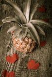Viele Valentinsgrußherzen mit Ananas auf dem alten Holztisch getont Lizenzfreies Stockbild