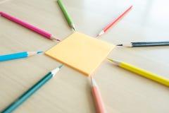 Viele verschiedenen farbigen Bleistifte setzten sich um Post-It auf hölzerne Rückseite Stockbilder