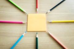Viele verschiedenen farbigen Bleistifte setzten sich um Post-It auf hölzerne Rückseite Lizenzfreies Stockbild