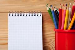 Viele verschiedenen farbigen Bleistifte und leeres Notizbuch auf Holztisch Stockbilder