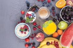 Viele verschiedenen Früchte und Beeren Vitamine und gesundes Lebensmittel Orangensaft in einem Glas, im Jogurt, im muesli mit Bee stockbild