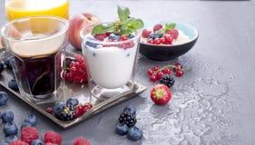Viele verschiedenen Früchte und Beeren Vitamine und gesundes Lebensmittel Orangensaft in einem Glas, im Jogurt, im muesli mit Bee stockfotos