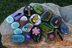 Viele verzierten die gemalten Felsen, die auf einem kleinen Flussstein angezeigt wurden Stockbild