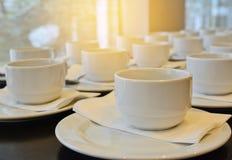 Viele weißen Kaffeetassen, die auf das Dienen mit Sonnenlicht-EFF warten Lizenzfreie Stockfotografie