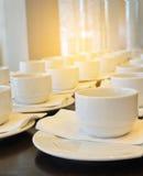Viele weißen Kaffeetassen, die auf das Dienen mit warmem hellem E-F warten Stockbilder