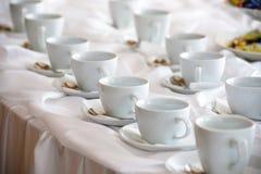 Viele weißen Kaffeetassen in einer Linie über einem Buffet stockfoto