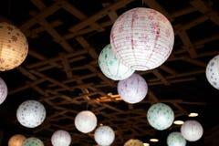 Viele weißen runden chinesischen Papierlaternen, die in der Dunkelheit hängen Stockfotografie