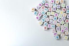 Viele Weißwürfel mit Buchstaben auf einem weißen Hintergrund Stockfotografie