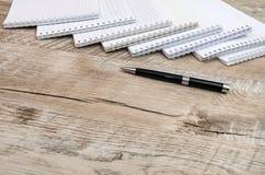 Viele weißen Notizbücher und ein Stift auf einem hölzernen Hintergrund lizenzfreies stockbild