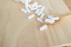 Viele weißen Pillen/Tabletten/Medizin auf hölzerner Platte Lizenzfreie Stockfotos