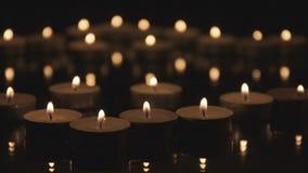 Viele Weihnachtskerzen, die in der Dunkelheit brennen stock footage