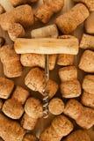 Viele Weinkorken und -korkenzieher auf dem hölzernen Hintergrund Lizenzfreie Stockbilder