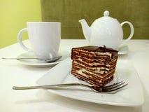 Vielschichtiger Spartak Cake auf der Platte nahe bei der Schale und der Teekanne Stockbild