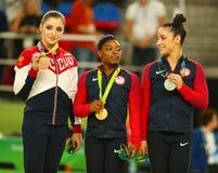 Vielseitige Gymnastiksieger in Rio 2016 Olympische Spiele Aliya Mustafina L, Simone Biles und Aly Raisman während der Medaillenze Stockfotografie