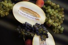 Vielzahl des bunten Sommers trägt Hintergrund Früchte: Trauben, Melone, Pfirsiche lizenzfreie stockbilder