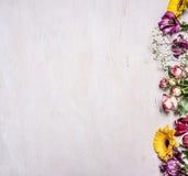 Vielzahl des Frühlinges blüht, gelbe Rosen, die Strauchrosen, Freesie, Sonnenblumen, Grenze, Platz für Text auf hölzernem rustika Lizenzfreies Stockfoto