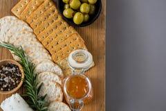 Vielzahl des Käses mit Oliven, Honig, Rosmarin, Walnüssen und Crackern Lizenzfreie Stockfotografie