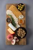 Vielzahl des Käses mit Oliven, Pfirsich, Honig, Rosmarin, Walnüssen und Crackern Stockfoto