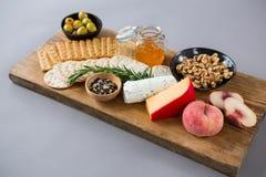 Vielzahl des Käses mit Oliven, Pfirsich, Honig, Rosmarin, Walnüssen und Crackern Stockfotografie