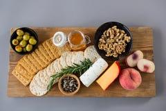Vielzahl des Käses mit Oliven, Pfirsich, Honig, Rosmarin, Walnüssen und Crackern Stockbilder