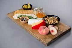 Vielzahl des Käses mit Oliven, Pfirsich, Honig, Rosmarin, Walnüssen und Crackern Lizenzfreies Stockbild