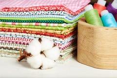 Vielzahl von Baumwolltextilien, von Baumwollblume und von Holzkiste mit Thread Lizenzfreie Stockfotografie