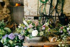 Vielzahl von Blumen in den hölzernen backets Bouquetes, das auf Holztisch steht Zusammensetzung mit Blumen mit angenehmem Geruch  stockfotografie