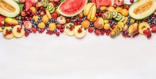 Vielzahl von bunten organischen Früchten und von Beeren auf weißem Tabellenhintergrund, Draufsicht, Grenze Gesunde Nahrung Lizenzfreie Stockfotografie