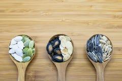 Vielzahl von essbaren Samen im hölzernen Löffel auf hölzernem Hintergrund Lizenzfreie Stockfotos