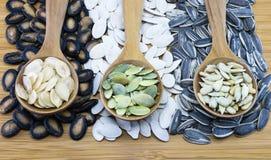 Vielzahl von essbaren Samen im hölzernen Löffel auf hölzernem Hintergrund Lizenzfreie Stockfotografie