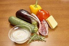 Vielzahl von Gemüse Bestandteilen für das Kochen auf hölzernem rustikalem Draufsichtkäseauberginenpfefferöl-Saftlamm des Hintergr Stockfotos