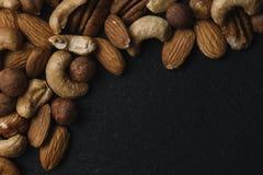 Vielzahl von Mischnüssen - Mandel, Haselnüsse und Acajoubaum - auf dem dunklen Schieferhintergrund mit Kopienraum Beschneidungspf Stockfoto