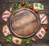 Vielzahl von Sandwichen für einen Snack, Verbreitung heraus um den runden Schneidebrettplatztext, Rahmen auf die hölzerne rustika Stockbilder