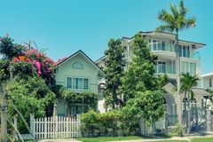 Ne beautiful three-story house with palm trees, trees, and landscape design in the summer royalty free stock photos