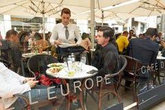 Viena, Áustria - 15 de abril de 2018: Um café da rua Garçom e visitantes em tabelas fotografia de stock royalty free