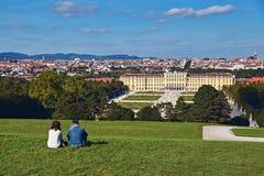 Viena, Áustria - 24 de setembro de 2014: Pares de turistas que sentam-se na grama com a vista do palácio de Schonbrunn Imagens de Stock
