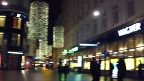 VIENA, ÁUSTRIA - DEZEMBRO, 24 filtra o tiro de lojas luxuosas de Louis Vuitton, de Wagner e de Rolex na noite vídeo 4K vídeos de arquivo