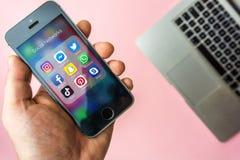 Viena Áustria - março 20 2019, mulher que guarda o SE de Apple com ícones de meios sociais na tela Os meios sociais são a maioria imagens de stock
