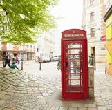 Viena, Áustria A menina na cabine de telefone vermelha imagens de stock royalty free