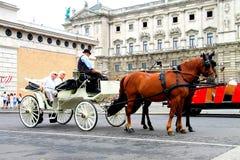 Viena, Áustria, turistas idosos monta em um treinador de passeio e escuta a história de um cocheiro-guia Foto de Stock