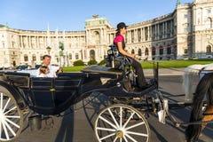 La gente tiene un paseo en el carro traído por caballo, llamado fiaker, en Viena Fotos de archivo